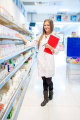 Beautiful blonde pharmacist in drugstore or pharmacy