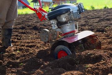 Farmer using modern mechanical rotary tiller with plow