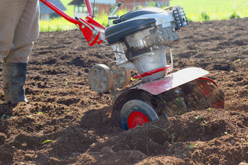 Farmer using modern mechanical rotary tiller with plow