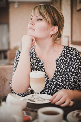 Girl sitting in a cafe drinking coffee