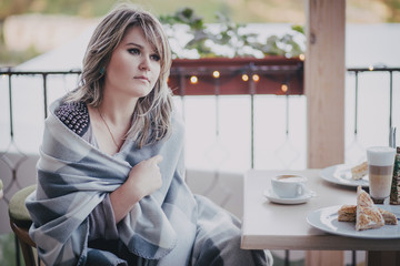 Girl sitting in a cafe wrapped in blanket