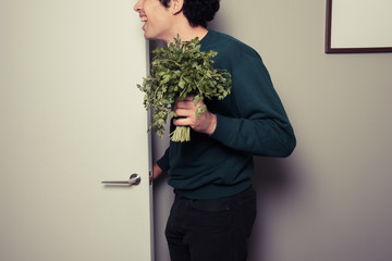 Happy man with parsley is answering the door