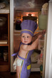 Little boy in a chief hat standing near refrigerator