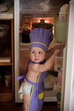 Little boy in a chief hat standing near refrigerator