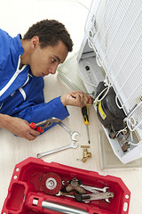 Repairman makes refrigerator appliance maintenance works