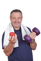 Elderly man with apple and dumbbells