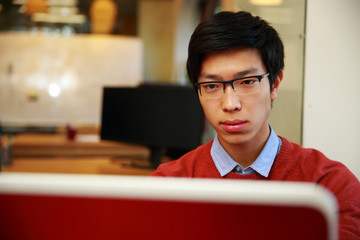 Young asian man in glasses working on laptop