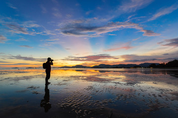 Photographer take a photo on colorful sunset