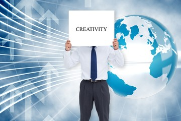 Businessman holding card saying creativity
