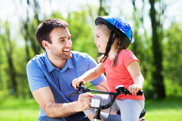 Girl learning to ride a bicycle with father