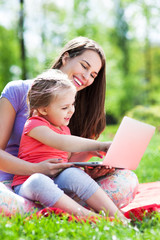 Mother and daughter using laptop outdoors