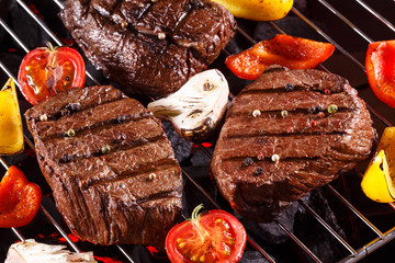 Juice Beef steak on a barbecue grill with vegetables