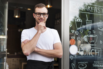 Portrait of smiling male waiter outside the cafe