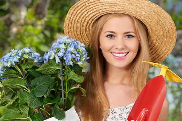 Hübsche junge Frau mit Blumen und Gartengeräten.