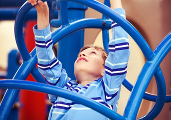 Beautiful child playing on colorful playground climbing up