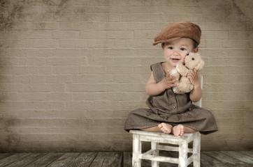 Kind mit Teddy auf einem Stuhl