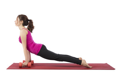 Young woman doing upward facing dog with dumbbells