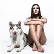 Naked brunette sitting with husky