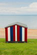 Striped beach hut on grass, by the sea