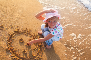 little girl draws sun on sand at the beach