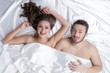 Cheerful heterosexual couple posing in bed