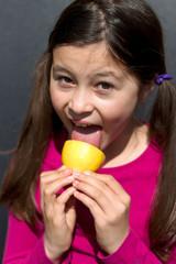 junges Maedchen leckt an einer Zitrone