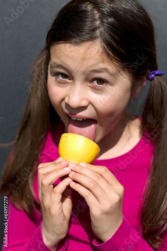 canvas print picture junges Maedchen leckt an einer Zitrone
