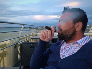 man smoking cigar on the hotel terace