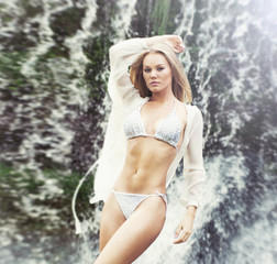 Attractive, fit, young and sexy girl posing near a waterfall