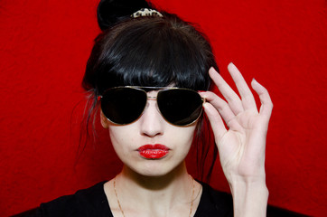 The girl with brightly red lipstick and in dark glasses