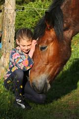 Mädchen schmust mit Pferdekopf