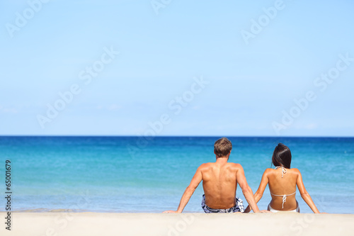 Couple on beach sitting in sand looking at sea