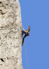Happy woman climbing rock, active holidays.