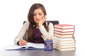 Portrait of  bored schoolgirl doing his homework at desk