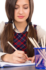 Closeup of  student sitting at her desk concentrated and doing h