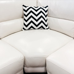 White leather sofa with decorative cushion
