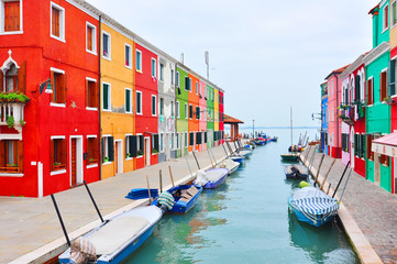 Burano island canal, colorful houses church. Italy.