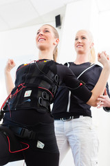 Frau beim EMS Training mit Trainerin
