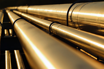 golden steel pipeline during sunset
