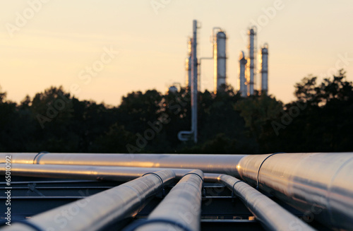Leinwanddruck Bild silhouette  of crude oil refinery station during sunset with lon