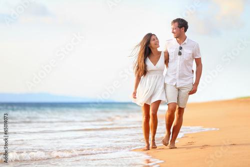 Beach couple walking on romantic travel - 65014073