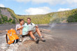 Couple hiking on volcano on Hawaii looking at map