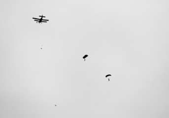 retro  biplane with skydivers in black and white