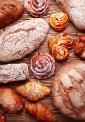 Bread and buns over wooden background