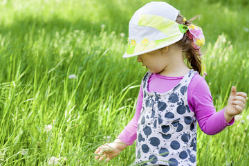 Little girl in a color hat plays on the green meadow.