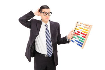 Confused young businessman holding an abacus