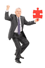 Joyful mature businessman holding piece of puzzle