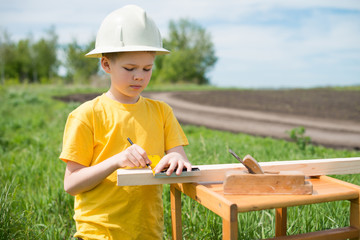 Little carpenter measuring timber.