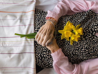 Dead womans crossed hands holding flowers
