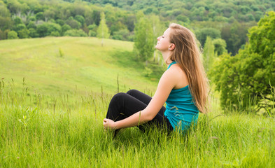 Girl relaxing on green grass. Happy woman sitting on the hill.